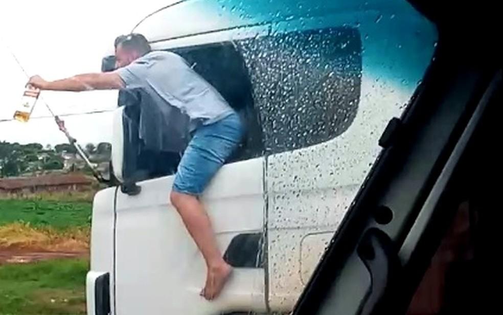 Caminhoneiro é filmado com corpo para fora de veículo com garrafa de bebida na mão enquanto dirige 18